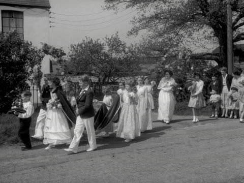 A May Queen leads a procession of children through the village of Hartwell during the May Day celebrations