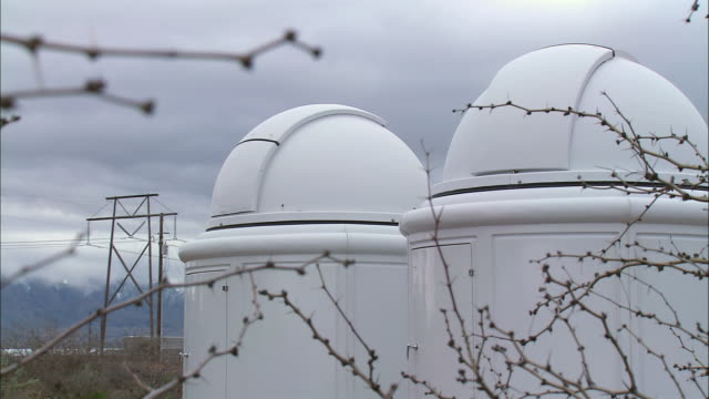 vidéos et rushes de may la two mini observatories through the branches of trees / new mexico, united states - télescope astronomique