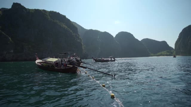 maya bay, the beach with long-tail boats and tourists at christmas, phi phi lay island, krabi province, thailand, southeast asia, asia - insel phi phi le stock-videos und b-roll-filmmaterial
