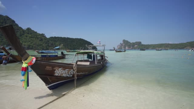 maya bay, the beach with long-tail boats and tourists at christmas, phi phi lay island, krabi province, thailand, southeast asia, asia - thailand stock videos & royalty-free footage