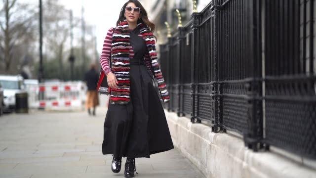 maya williams wears sunglasses, a color striped scarf, a red and white striped top, a black dress, black shoes, during london fashion week february... - black dress stock videos & royalty-free footage