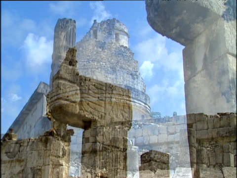 mayan ruins on sunny day with blue sky. stone structures and carvings on wall. chichen itza - chichen itza stock videos and b-roll footage