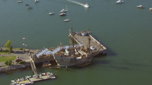 ws aerial pov mayflower ii ship and nautical vessels moored at plymouth harbour/ plymouth, massachusetts, united states - massachusetts stock-videos und b-roll-filmmaterial