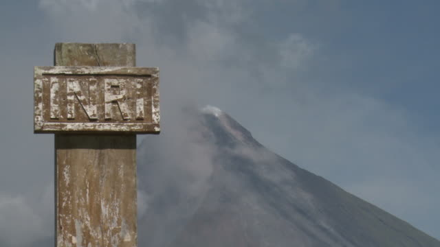 Mayon volcano smoulders behind religious sign on cross, Philippines, Dec 2009