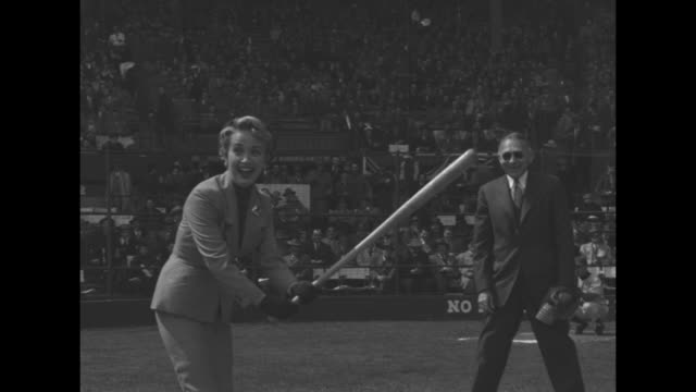 ms mayor allen lamport draws arm back getting ready to pitch the ball / ms actress jane powell holds bat getting ready to take swing / ms lamport... - jugendmannschaft stock-videos und b-roll-filmmaterial