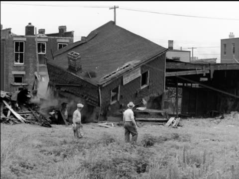 / mayor Fiorello La Guardia of New York City operating machine ripping down slums in New York / crane loading trucks buildings falling / new...