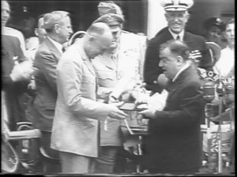 Mayor Fiorello La Guardia presents a medal to Dwight Eisenhower behind a bank of microphones as uniformed officers rise to applaud in the background...