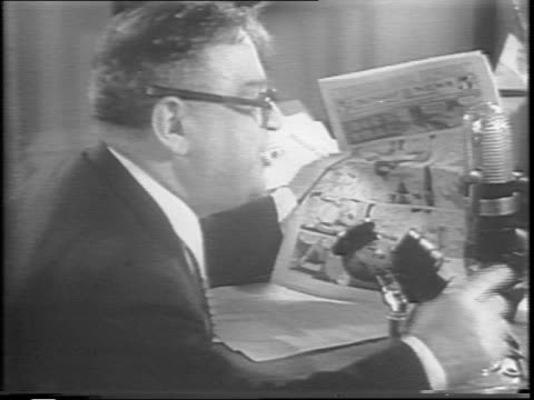 Mayor Fiorello La Guardia reads from a Dick Tracy comic strip into a bank of microphones one of which is adorned with the logo 'WNYC'