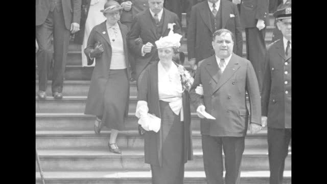 mayor fiorello la guardia walks down steps outside city hall with french first lady marguerite lebrun who holds his arm an nypd officer escorts them... - fiorello la guardia stock videos & royalty-free footage