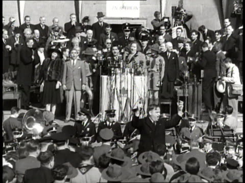 Mayor Fiorello LaGuardia leads the band as Irving Berlin and Kate Smith sing on stage before a large crowd