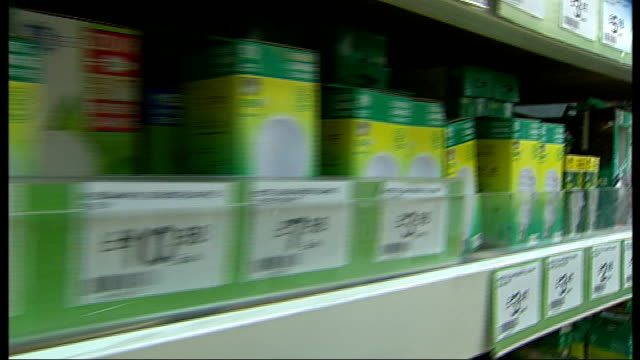 mayor of london launches energysaving lightbulb initiative boxes of energysaving lightbulbs for sale on shop shelves close up of lightbulb with lit... - energy efficient lightbulb stock videos and b-roll footage