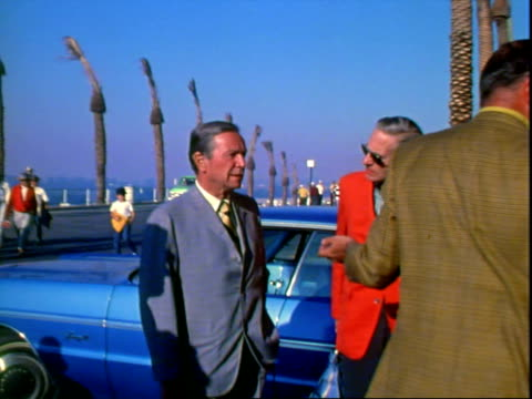 Mayor of Los Angeles Sam Yorty wearing light gray suit tacky yellow and blue striped tie while standing and talking with several middleaged men...