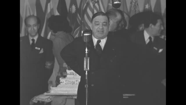 Mayor of New York City Fiorello H LaGuardia at Stage Door Canteen microphone in front of cake tells funny anecdote audience laughs in back of cake...
