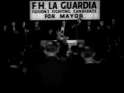 Mayoral campaign meeting speakers lined up on stage with FH LaGuardia banners audience standing cheering applauding and singing when LaGuardia is...
