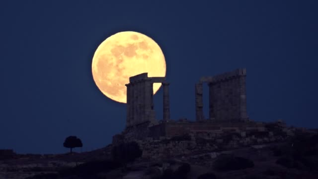 may's full moon also called flower moon rises behind the ancient temple of poseidon in cape sounion southeast of athens greece on 29 may 2018 - sounion stock videos and b-roll footage