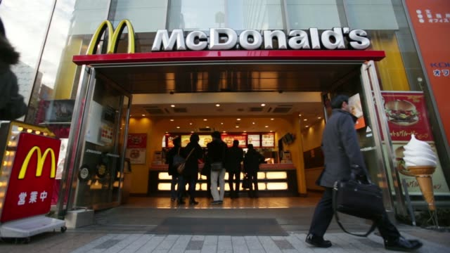 mcdonald's corp signage is displayed outside one of the company's restaurants in tokyo japan on wednesday feb 5 pedestrians walk past a mcdonald's... - mcdonald's stock videos & royalty-free footage