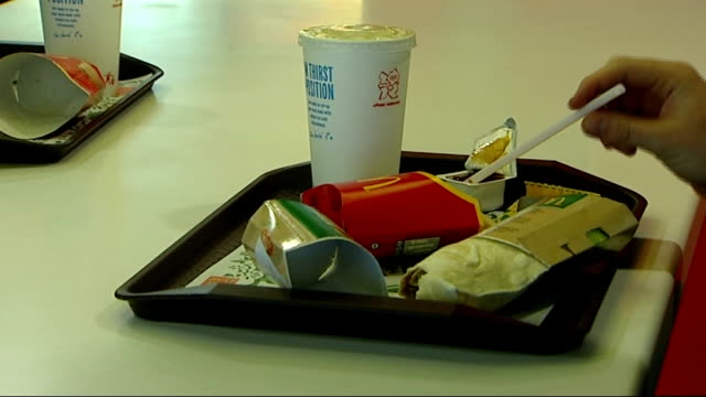 McDonald's fast food restaurant calorie displays and GVs Close shot of person seated at table in McDonald's with McDonalds paper bags and food...