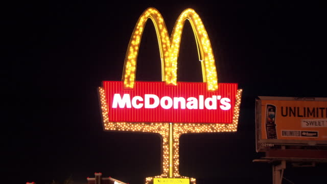 a mcdonald's sign flashes on the las vegas strip. - ファーストフード点の映像素材/bロール