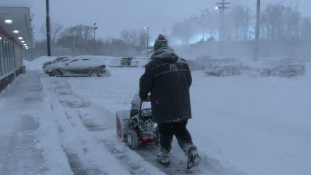 a mcdonald's store manager uses a snowblower to clear deep snow from a parking lot in adams new york during a heavy lake effect snowstorm - scott mcpartland stock videos & royalty-free footage