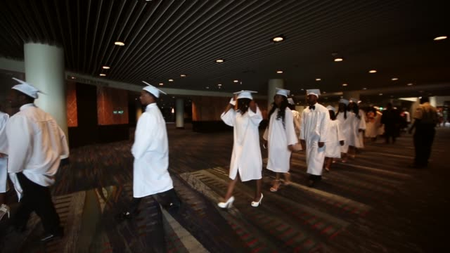 mcdonogh senior high school graduates walk at their commencement at the ernest n morial convention center on may 14 2015 in new orleans louisiana... - sekundarstufe stock-videos und b-roll-filmmaterial
