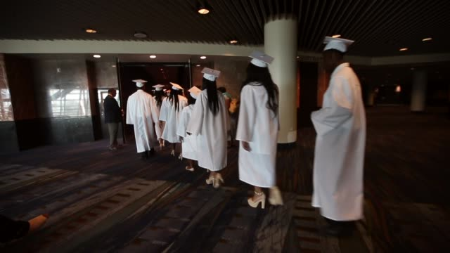 mcdonogh senior high school graduates walk at their commencement at the ernest n morial convention center on may 14 2015 in new orleans louisiana... - toga stock videos and b-roll footage