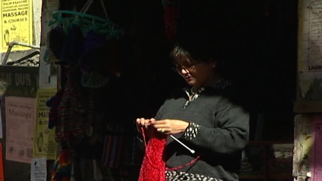 mcleod ganj. from a tibetan vendor standing in front of a shop and knitting yarn as pedestrians walk past. thousands of tibetan exiles live and work... - knitting needle stock videos & royalty-free footage