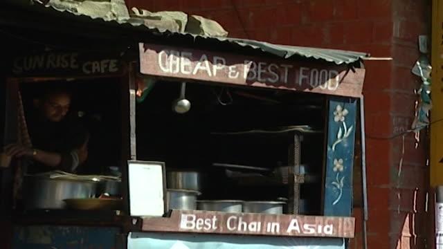 mcleod ganj. pan-left across street food vendors working in food kiosks. thousands of tibetan exiles live in mcleod ganj. - mestolo video stock e b–roll
