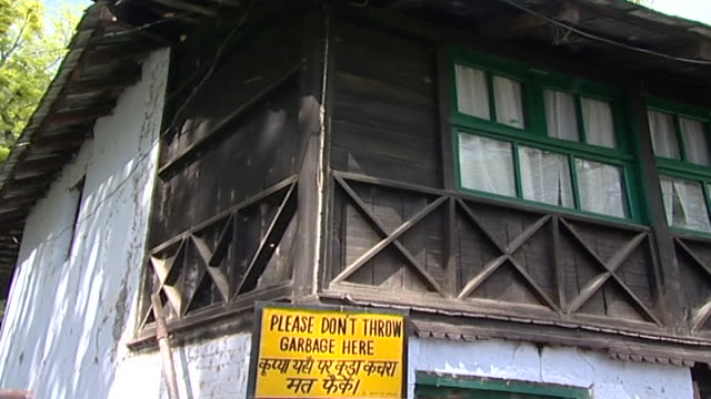 mcleod ganj. tilt down pan-left view of a home with a 'please don't throw garbage here' sign in english and tibetan. - traditionally tibetan stock videos & royalty-free footage