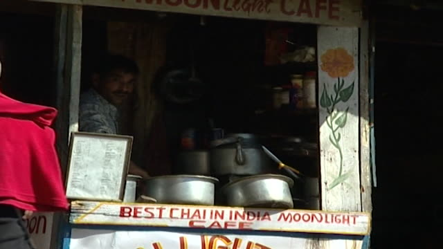 mcleod ganj. view of a street food vendor working in a kiosk named moonlight cafe and two tourists standing in front. thousands of tibetan exiles... - mestolo video stock e b–roll