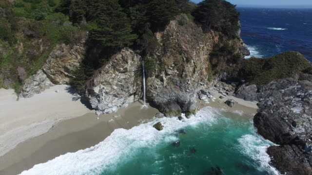 mcway falls cascades onto a pristine sandy beach in big sur's julia pfeiffer burns state park. - state park stock videos & royalty-free footage