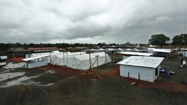 vídeos de stock, filmes e b-roll de ws médecins sans frontières rapidly expands their ebola case management facility at elwa 3 in monrovia liberia the center currently has 120 beds they... - ébola