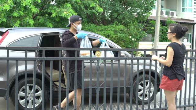 vidéos et rushes de service de livraison de repas par des hommes asiatiques livrés au client à la porte d'entrée en voiture - auto discipline