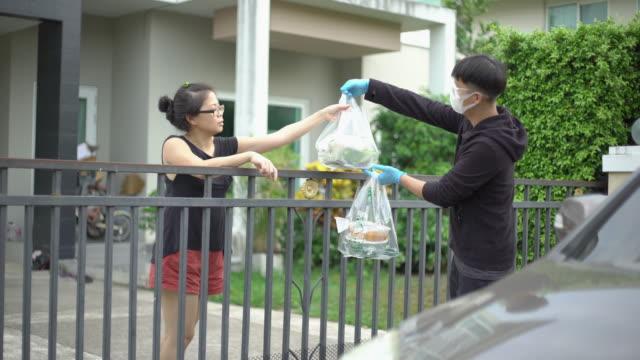måltid leverans service av asiatiska män levereras till kunden vid ytterdörren med bil - thailändskt ursprung bildbanksvideor och videomaterial från bakom kulisserna