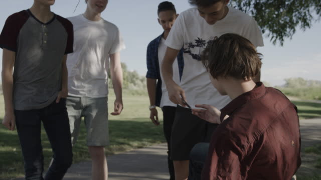 mean boys bullying boy in park and taking his cell phone / lehi, utah, united states - lehi stock videos & royalty-free footage