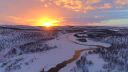 AERIAL: Meandering river flowing through gorgeous hilly winter landscape Lapland