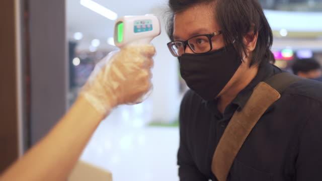 messen sie die temperatur vor dem betreten des restaurants während covid-19 corona virus neue normale - temperatur stock-videos und b-roll-filmmaterial