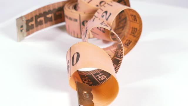 vidéos et rushes de mesurer la taille en rose isolé fond blanc. - tape measure
