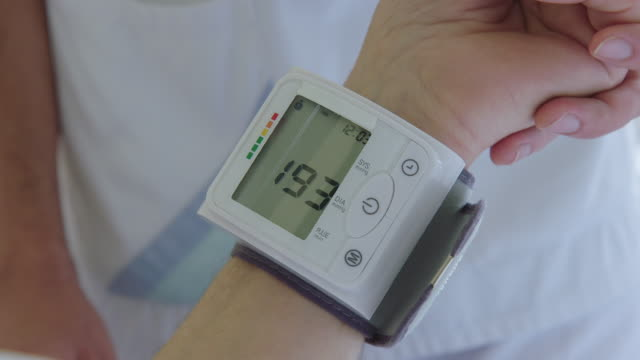 measuring blood pressure of patient in hospital bed - blood pressure gauge stock videos & royalty-free footage