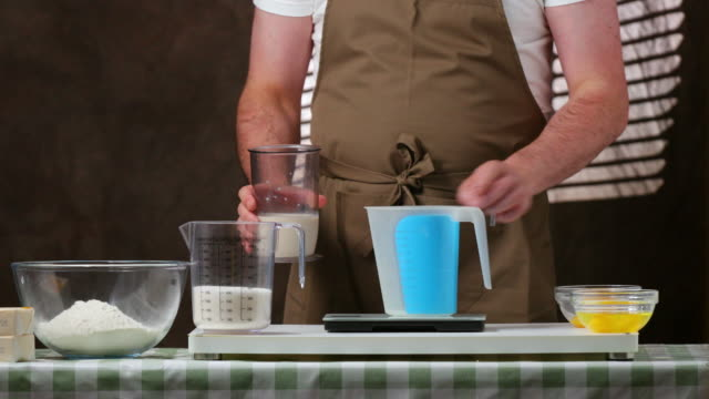 Measuring milk with sour cream in order to prepare a cake.