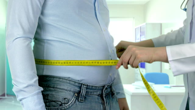 vídeos de stock e filmes b-roll de measuring overweight - 4k resolution - overweight