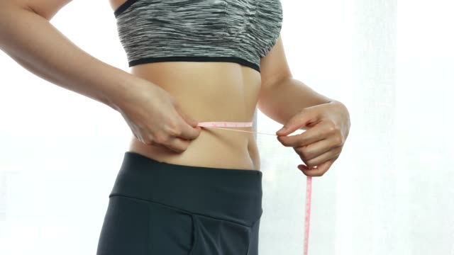 measuring waistline of a beautiful body in inches - dieting stock videos & royalty-free footage