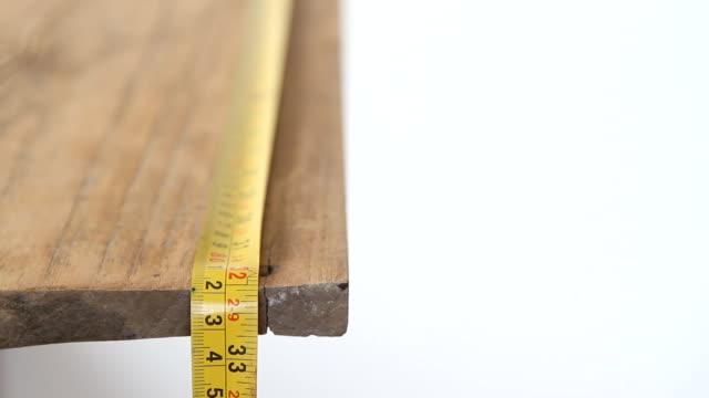 vidéos et rushes de mesure de bois avec du ruban de mesure - tape measure