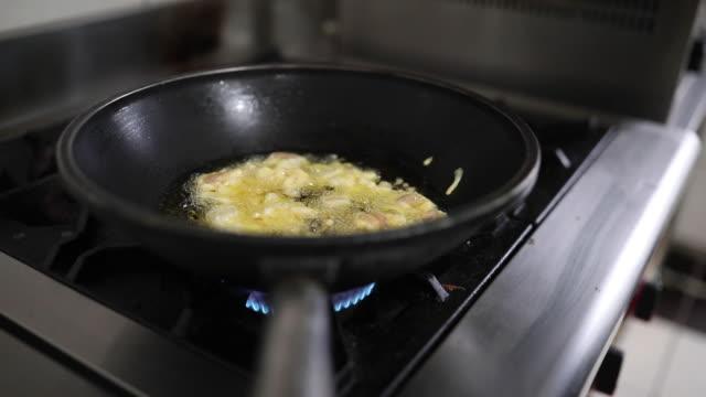 vídeos de stock, filmes e b-roll de fritura de carne em frigideira em um fogão - crocante