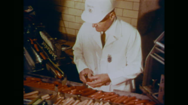 1966 usda meat inspector removes frankfurter hot dog from conveyor belt for testing - hot dog stock videos & royalty-free footage