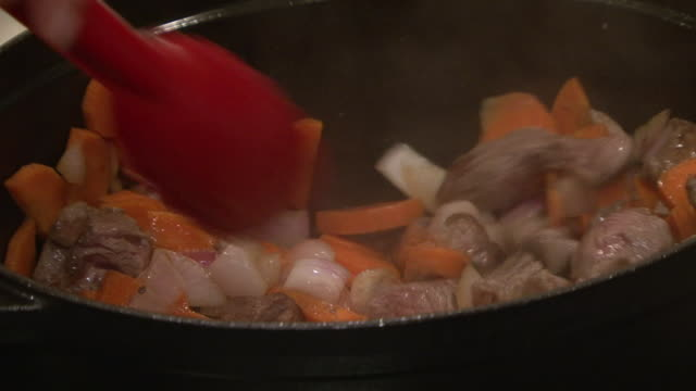meat, onion and carrots. on the hands of a chef using tongs to stir meat, onions and carrots in a pot on a stove. - gourmet stock videos & royalty-free footage