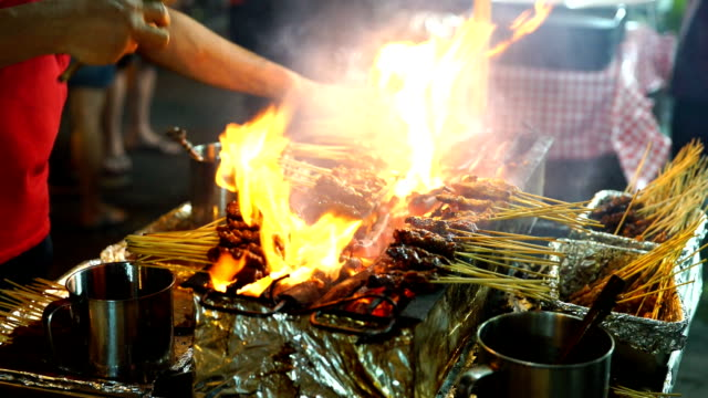 Meat skewers cook over hot coals in Singapore's Satay Street food market