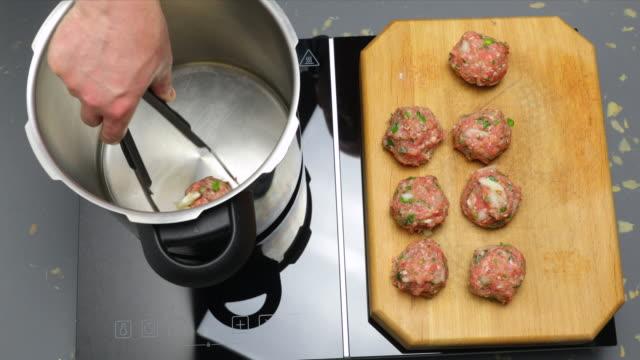 meatballs and tomato sauce in pressure cooker. - annick vanderschelden stock videos & royalty-free footage