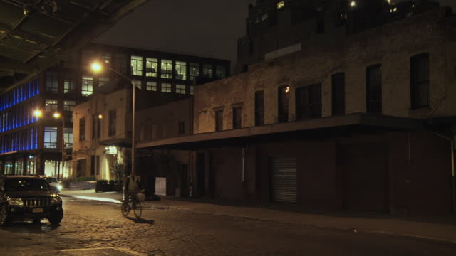 ms meatpacking district with warehouses and loft buildings, passing bicycle / new york, new york, usa - 屋根裏部屋点の映像素材/bロール