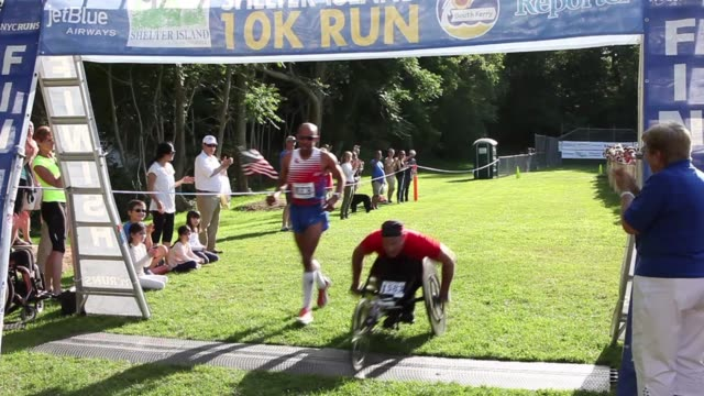 meb keflezighi america's top marathon runners competes in shelter island 10k meb crosses finish line with wheelchair athlete - salmini stock videos and b-roll footage
