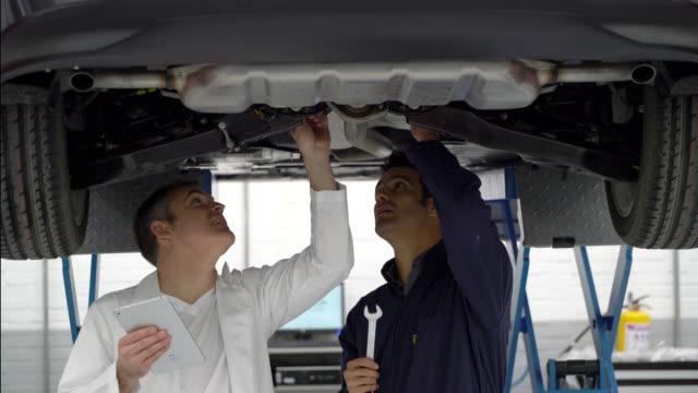 mechaniker und manager arbeiten unter einem auto blick auf die teile zu reparieren - in bodenhöhe stock-videos und b-roll-filmmaterial